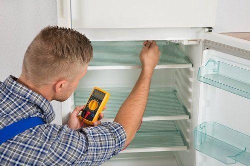 un tecnico che testa un frigorifero