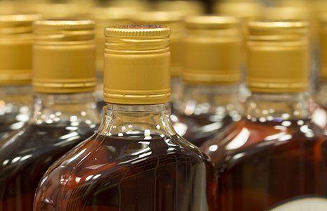 vista ravvicinata di alcune bottiglie di vetro che contengono un liquore di color marrone