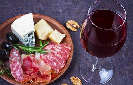 un piatto di affettati, grana, gorgonzola e olive nere e accanto un bicchiere di vino rosso e delle noci sgusciate sul tavolo