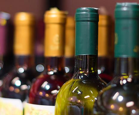 tre bottiglie di vino con visuale focalizzata sul collo delle bottiglie