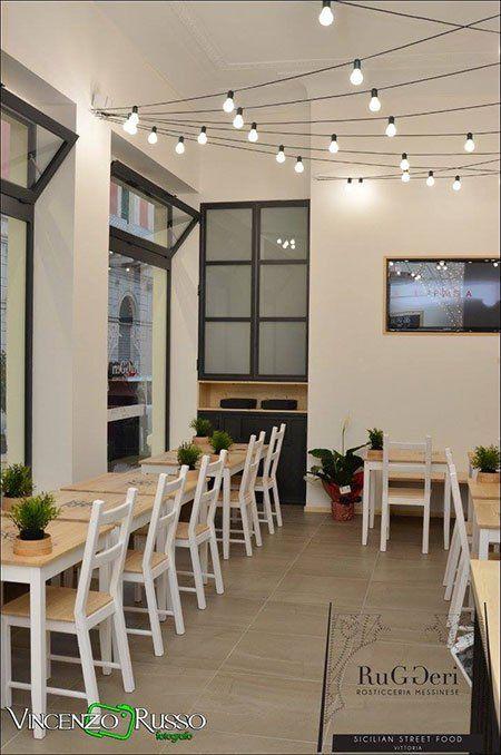 Interno del business, lampadine impiccando,piante nelle tavole