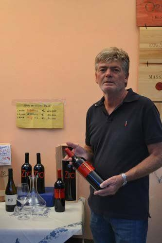 proprietari azienda agricola mostrano i loro vini pregiati