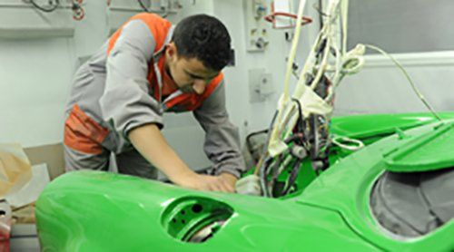 operaio in officina lavora su un auto verde