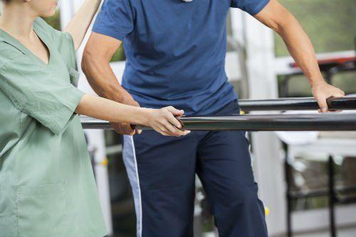 Paziente effettua un esercizio di riabilitazione deambulatoria appoggiandosi a delle sbarre