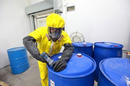 completamente protetti in divisa gialla, maschera e guanti professionale che si occupa di prodotti chimici