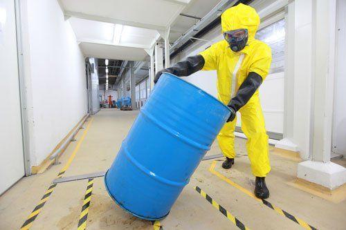 Operaio in uniforme di protezione, maschera, guanti e stivali di rotolamento barile di prodotti chimici