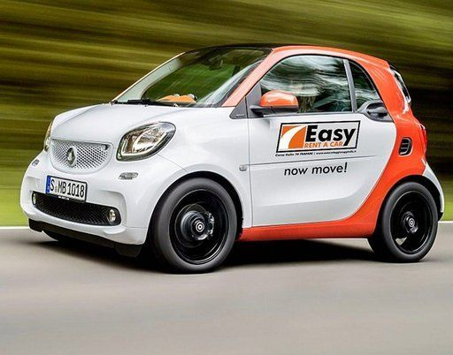 vista laterale di una macchina bianca con scritta EASY RENT CAR now move!