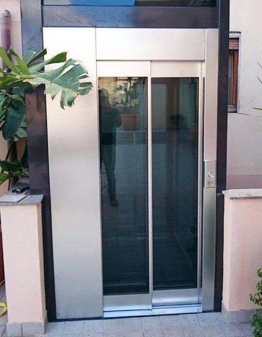 Ascensore esterna con vetrata e sulla sinistra si vede a malapena una pianta di color verde installazione ascensori, ascensori idraulici, ascensori elettrici, ascensori senza cavi, piattaforme elevatrici, manutenzione ascensori, progettazione ascensori Caltanissetta