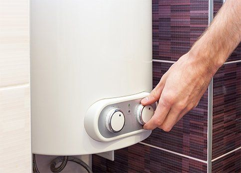 A man setting the temperature of a water in electric water heater