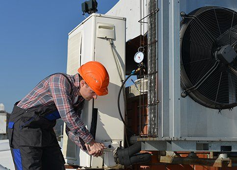 Young repairman fixing air conditioning system
