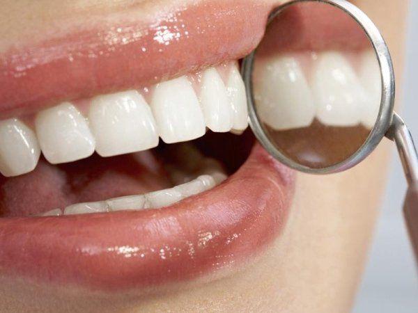 Denti con accanto specchietto del dentista