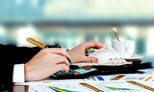 una mano con una penna,una calcolatrice e un quaderno ad anelli