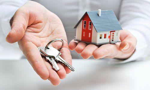 una mano con delle chiavi e l'altra con un modellino di una casa