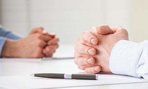 delle mani giunte appoggiate su un tavolo