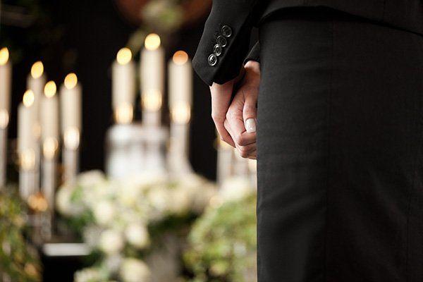 le mani di un uomo in piedi con un completo nero e di fronte delle candele accese