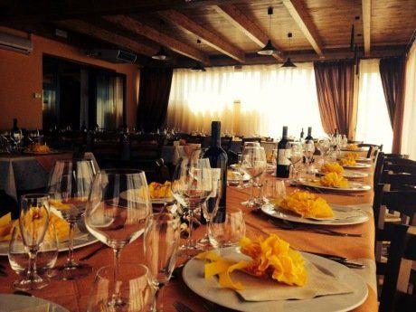 Lungo tavolo apparecchiato e con bottiglie di vino
