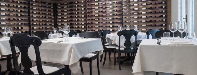 tavoli apparecchiati e scaffali con vini