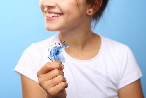 bambina con apparecchio per i denti in mano