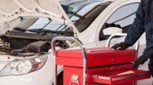 meccanico con carrello attrezzi si avvicina a un auto con il cofano aperto