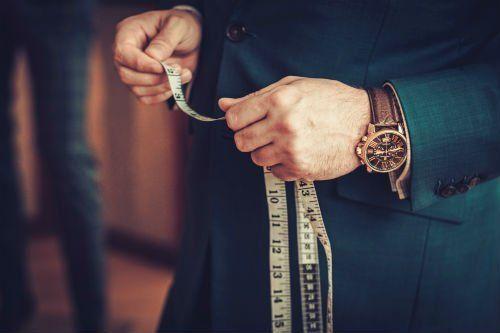 un sartoraio che misura dei vestiti