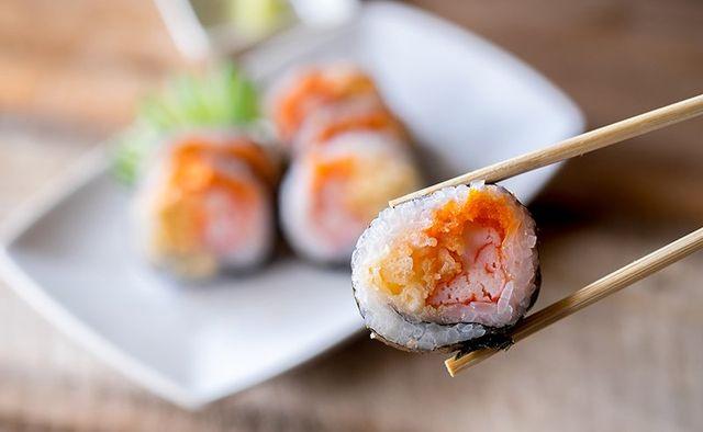 bacchette con un pezzo di sushi