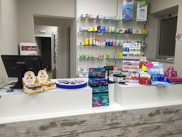il banco della farmacia con dei prodotti e dietro delle mensole con degli altri prodotti