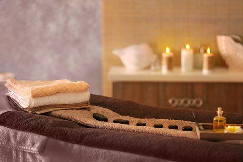 asciugamani piegati di color sabbia,bianchi, marroni e uno marrone disteso con sulla destra una boccetta di olio di essenza