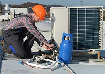a HVAC serviceman repairing an air conditioner on the roof of a building