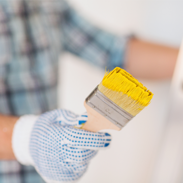 Man holding a paint brush with yellow paint on it