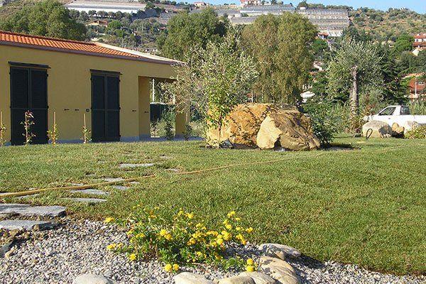 un giardino con delle rocce, prato, alberi e una casa gialla sulla sinistra