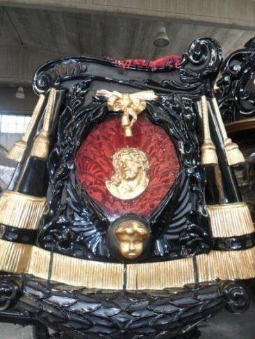 la statua dorata del volto di Cristo su una carrozza