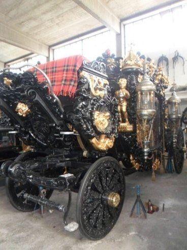 una carrozza nera con statue dorate