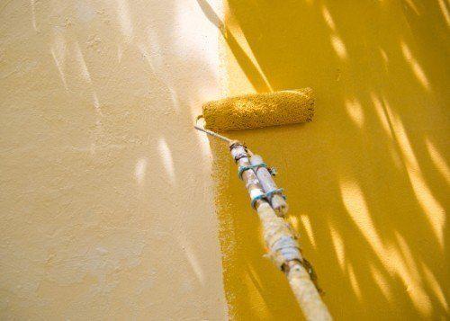 rullo per pitturare che sta riverniciando il muro
