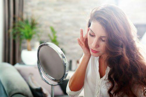 Donna allo specchio si massaggia le tempie