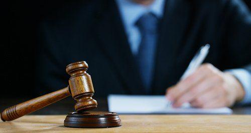 avvocato scrive con martello del giudice vicino