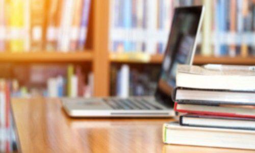 un pc e dei libri appoggiati su un tavolo in una libreria