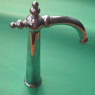 un rubinetto in acciaio appoggiato su un piano color turchese