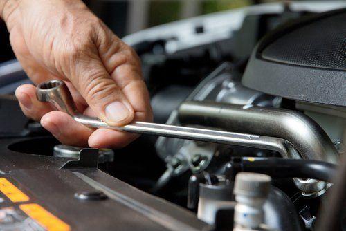 tecnico con chiave ad anello durante riparazione auto