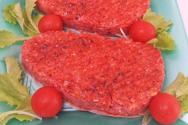 tre hamburger di carne crudi su un vassoio verde con pomodorini e foglie di lattugaa  Sant'Antonio Abate (NA)