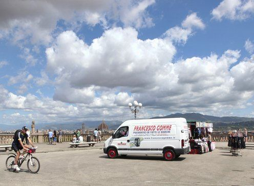 Furgoncino Francesco Gomme su ampio piazzale a Firenze, con turisti e cielo azzurro