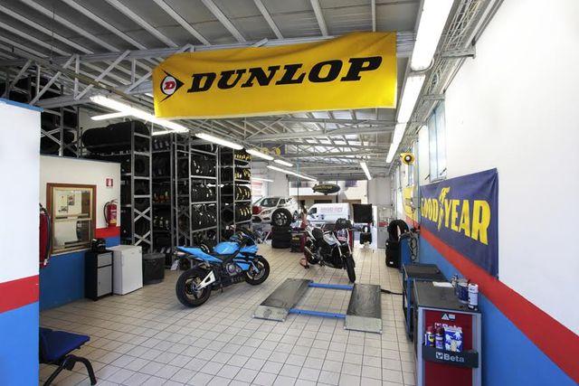 Una moto blu in vista sotto banner con marchio Dunlop