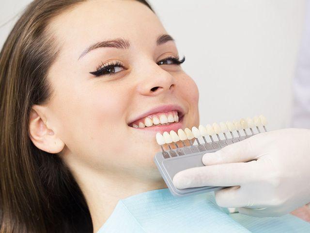 una ragazza sorridente e davanti una mano che sorregge una struttura con dei denti artificiali