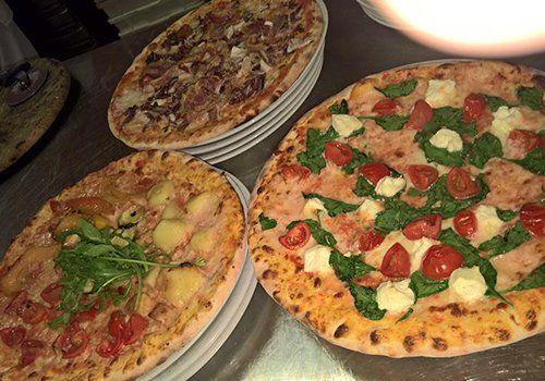 Pizze cotte in forno a legna con gli ingredienti come pomodoro mozzarella, basilico e patate