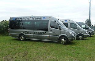3 northern travel minibuses parked side by side