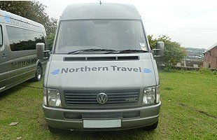 Grey northern travel minibus viewed from the front