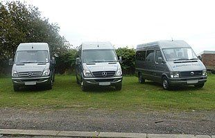 3 northern travel minibuses parked side by side viewed from the front