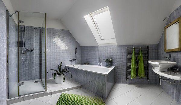 bagno con piastrelle grige, servizi, vasca e doccia