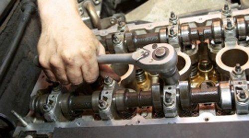 meccanico che lavora su un motore di un'auto