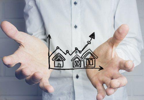 uomo con in mano un grafico di case che salgono di valore economico