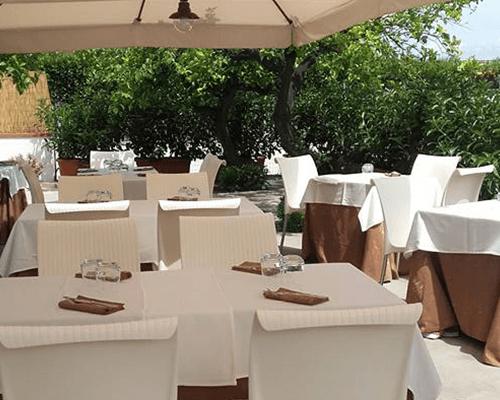 una terrazza con dei tavoli con delle tovaglie bianche